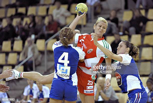 Hungary's Gabriella Szucs tries to throw the ball past France's Nina Kanto and Camille Ayglon during their GF World Cup match in Aarhus on October 14...