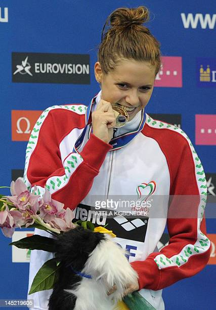 hungary's gold medallist Boglarka Kapas bites her medal after competing in the final of the women's 800metre freestyle swimming event in the 31st...