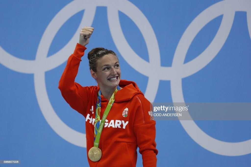 Hungary's Katinka Hosszu celebrates on the podium with her gold medal after she won the Women's 400m Individual Medley Final during the swimming event at the Rio 2016 Olympic Games at the Olympic Aquatics Stadium in Rio de Janeiro on August 6, 2016. / AFP / Odd ANDERSEN
