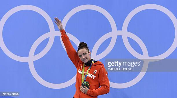 TOPSHOT Hungary's Katinka Hosszu celebrates with her gold medal on the podium after she won the Women's 100m Backstroke Final during the swimming...