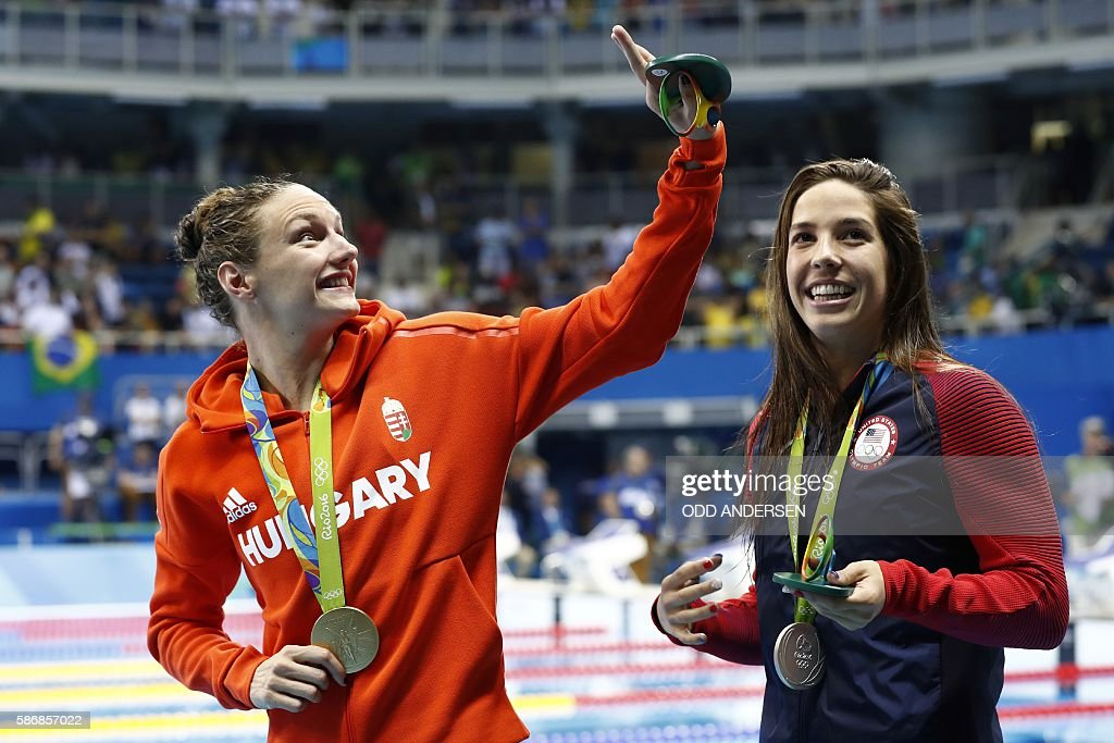 Hungary's Katinka Hosszu (L) waves next to silver medallist USA's Madeline 'Maya' Dirado after she won the Women's 400m Individual Medley Final during the swimming event at the Rio 2016 Olympic Games at the Olympic Aquatics Stadium in Rio de Janeiro on August 6, 2016. / AFP / Odd ANDERSEN
