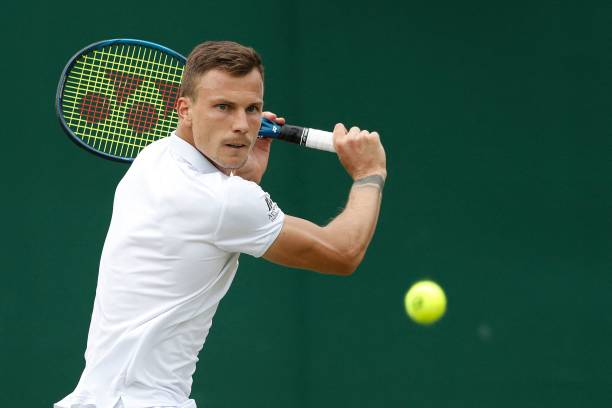 Hungary's Marton Fucsovics returns against Russia's Andrey Rublev during their men's singles fourth round match on the seventh day of the 2021...