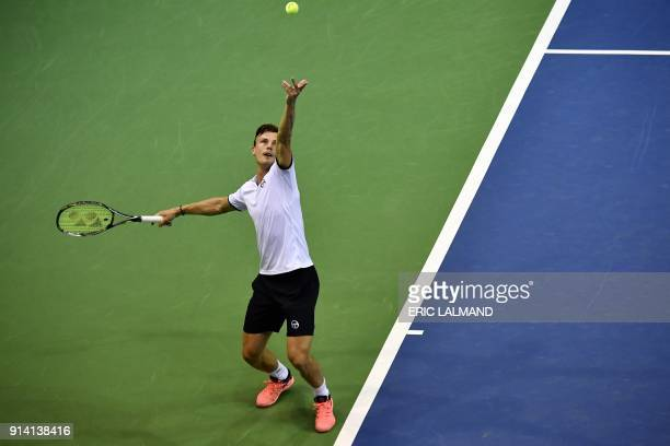 Hungary's Marton Fucsovics serves to Belgium's David Goffin during their tennis match as part of the Davic Cup World group tie between Belgium and...