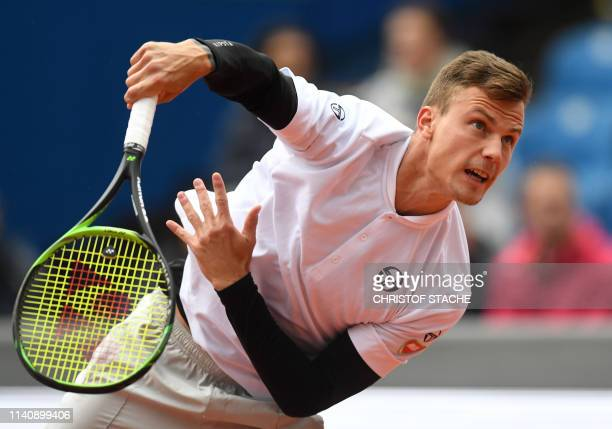 Hungary's Marton Fucsovics serves to Italy's Marco Cecchinato during their quarter final match at the ATP tennis Open in Munich southern Germany on...