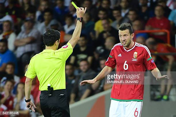 Hungary's midfielder Akos Elek reacts as he receives a yellow card from Serbian referee Milorad Mazic during the Euro 2016 round of 16 football match...
