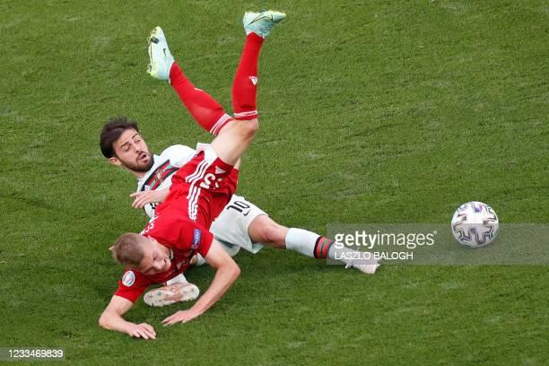 Hungary's midfielder Andras Schafer falls over Portugal's midfielder Bernardo Silva during the UEFA EURO 2020 Group F football match between Hungary...