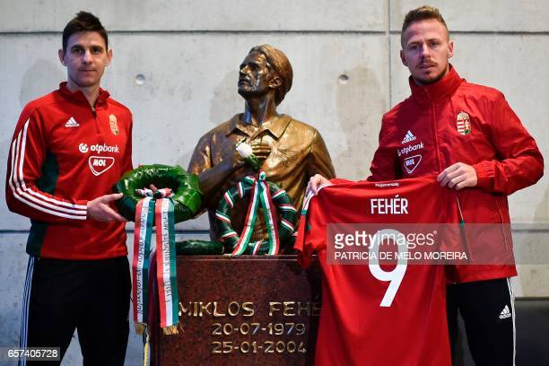 Hungary's midfielder Zoltan Gera and teammate forward Balazs Dzsudzsak pay tribute to late Hungarian player and former Benfica player Miklos Feher...