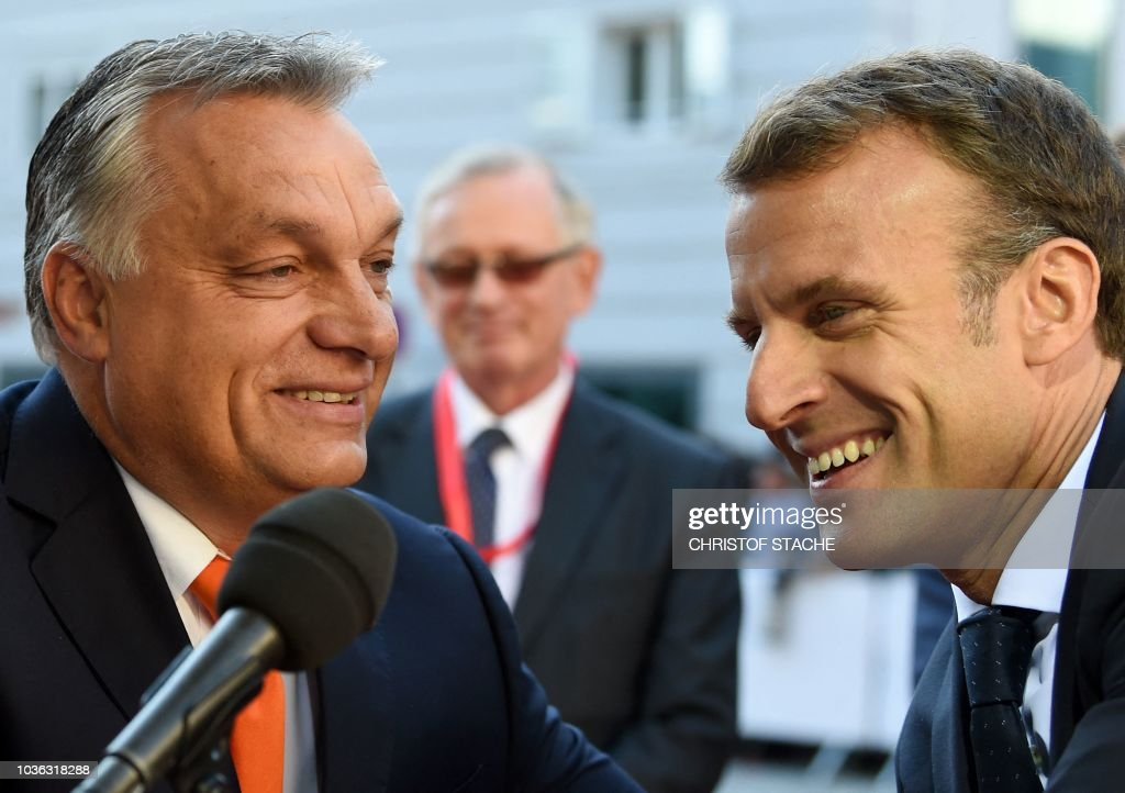 Hungary's Prime Minister Viktor Orban (L) and France's President Emmanuel Macron share a smile as they arrive at the Mozarteum University to attend a plenary session part of the EU Informal Summit of Heads of State or Government in Salzburg, Austria, on September 20, 2018.