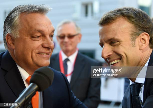 Hungary's Prime Minister Viktor Orban and France's President Emmanuel Macron share a smile as they arrive at the Mozarteum University to attend a...