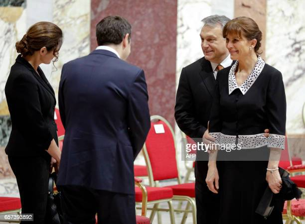 Hungary's Prime Minister Viktor Orban and his wife Aniko Levai talk to Greece's Prime Minister Alexis Tsipras and his wife Peristera Baziana before...
