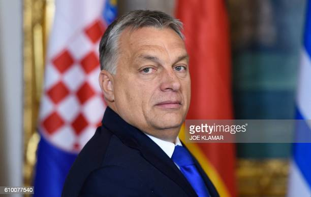 Hungary's Prime minister Viktor Orban is welcomed by the Austrian chancellor upon arrival for a meeting of leaders of countries along the Balkan...