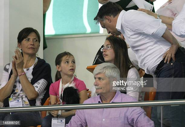 Hungary's Prime Minister Viktor Orban kisses one of his daughters as his wife jurist Aniko Levai looks on during the last evening of the swimming...