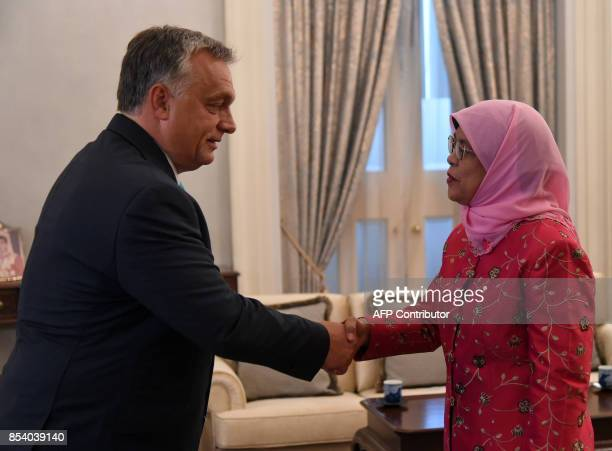Hungary's Prime Minister Viktor Orbán shakes hands with Singapore President Halimah Yacob during a meeting at Istana presidential palace in Singapore...