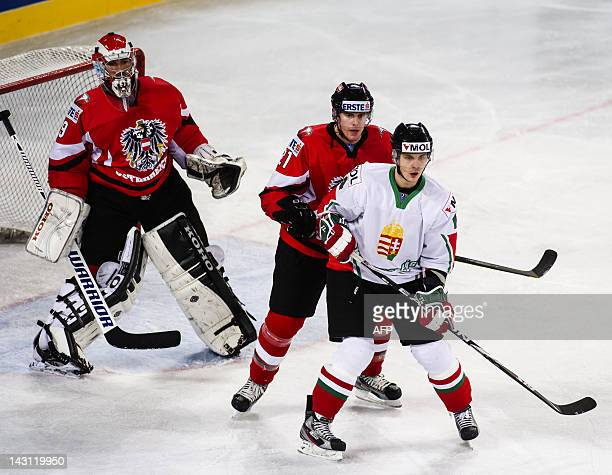 Hungary's Tamas Pozgai vies with Austria's Matthias Tratnig and Bernhard Starknbaum during the 2012 IIHF Ice Hockey World Championship Div I Group A...