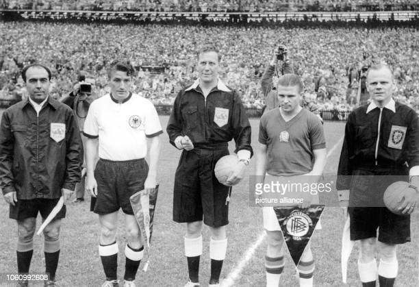 Hungary's team captain Ferenc Puskas and Germany's team captain Fritz Walter are standing between referee William Ling and linesmen Vincenzo...