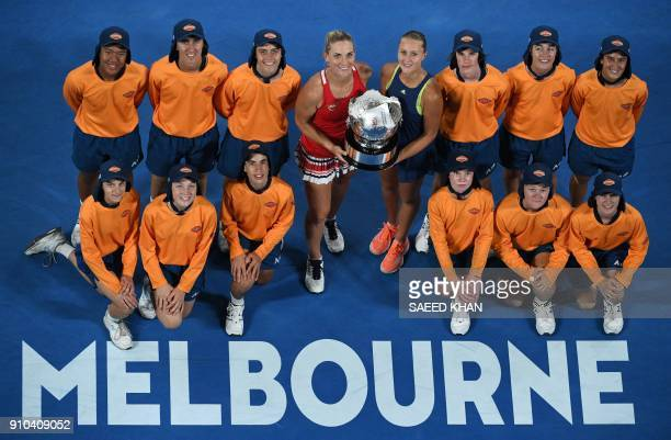 Hungary's Timea Babos and France's Kristina Mladenovic pose with the winners trophy and ballboys while celebrating after victory over Russia's...