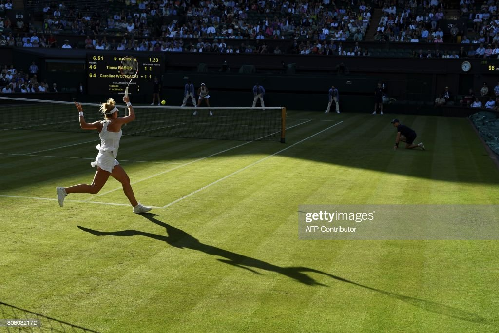 TOPSHOT - Hungary's Timea Babos (L) returns against Denmark's Caroline Wozniacki (R) during their women's singles first round match on the second day of the 2017 Wimbledon Championships at The All England Lawn Tennis Club in Wimbledon, southwest London, on July 4, 2017. / AFP PHOTO / Glyn KIRK / RESTRICTED