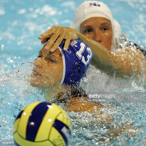 Hungary's Timea Benko is detained by Canada's Ann Dow during their women's water polo semifinal match at the XI FINA World Swimming Championships in...