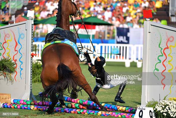 TOPSHOT Hungary's Zsofia Foldhazi tries to hold onto her horse after crashing into an obstacle in the show jumping portion of the women's modern...