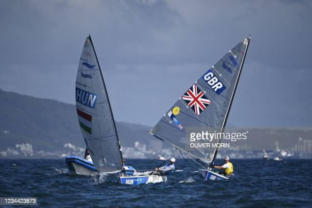 Hungary's Zsombor Berecz and Great Britain's Giles Scott compete in the men's one-person dinghy finn race during the Tokyo 2020 Olympic Games sailing...