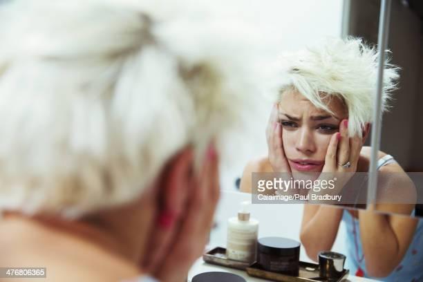 Hungover femme examiner elle-même dans le miroir