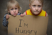 A hungry boy and a girl with a cardboard tablet with the inscription I'm hungry .