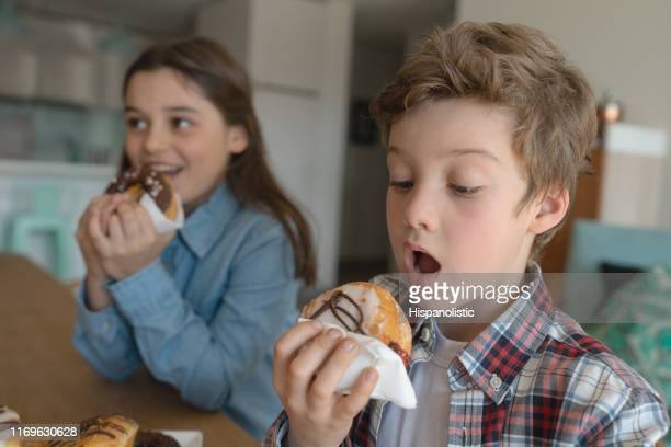 hungry brother and sister at home enjoying donuts - fat people eating donuts stock pictures, royalty-free photos & images