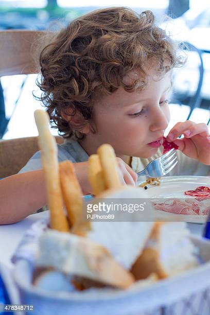 Hungry Child eats using fork and hands