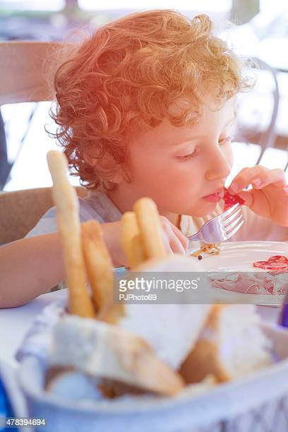 hungry child eats using fork and hands - pjphoto69 stockfoto's en -beelden