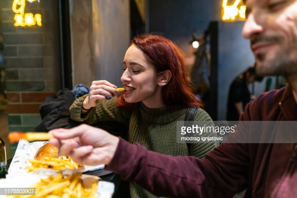 hungry couple in fast food restaurant - fast food french fries stock pictures, royalty-free photos & images