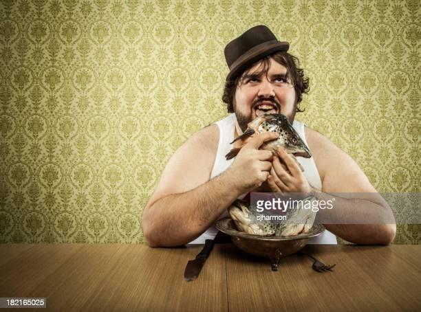 Hungrig Fett Mann lecken fish head Suppe auf Holz Tisch