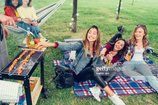 hongerige meisjes genieten van voedsel van de barbecue-grill - ongeduldig stockfoto's en -beelden