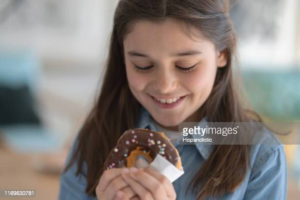 hungry little girl looking at her donut with excitement ready to eat it - fat people eating donuts stock pictures, royalty-free photos & images