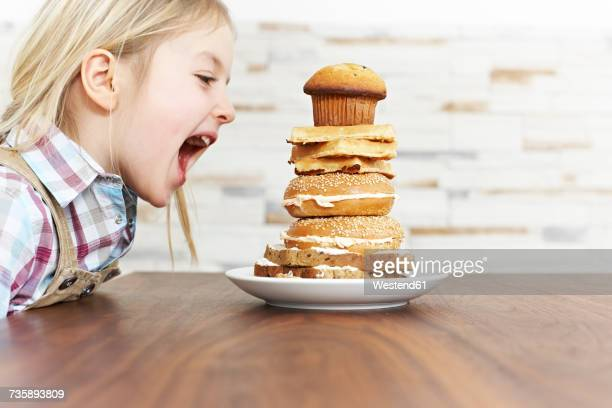 Hungry little girl with stack of baked goods