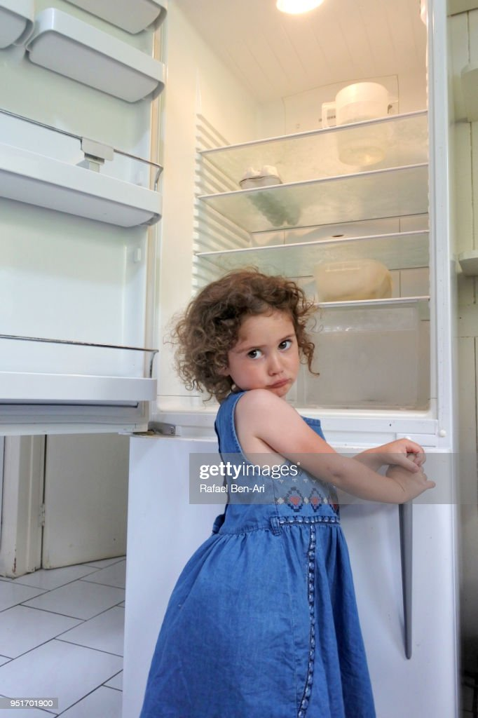 Hungry poor little girl looks for food in empty fridge at home : Stock Photo