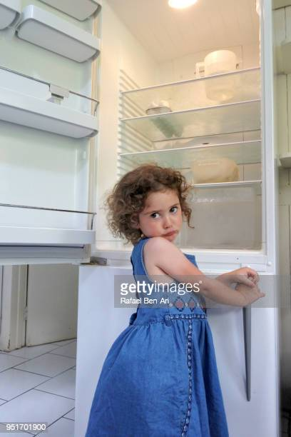 Hungry poor little girl looks for food in empty fridge at home