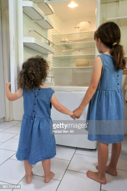 Hungry poor little sister girls looking for food in empty fridge at home