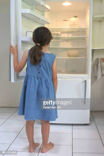 Hungry poor sister girl looks for food in empty fridge at home