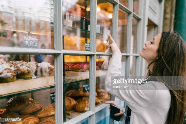 hungry woman at the bakery - shop window stock pictures, royalty-free photos & images