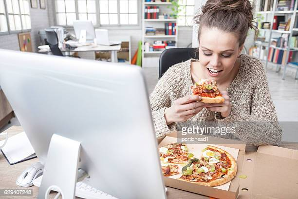 Hungry young woman having lunch break at the office