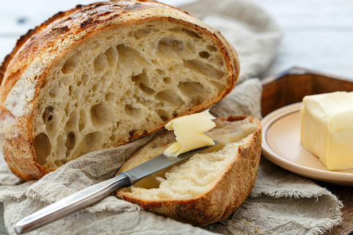 Hunk of French artisanal bread and a knife with butter. 954804872
