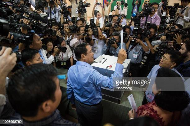 HunSenCambodia'sprimeministerandpresidentofCambodianPeople'sParty center holds up his ballot for the general election at a polling station...