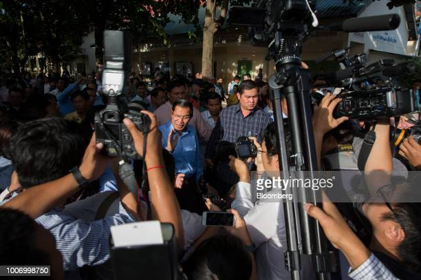 HunSenCambodia'sprimeministerandpresidentoftheCambodianPeople'sParty center waves as he leaves a polling station after casting his ballot...