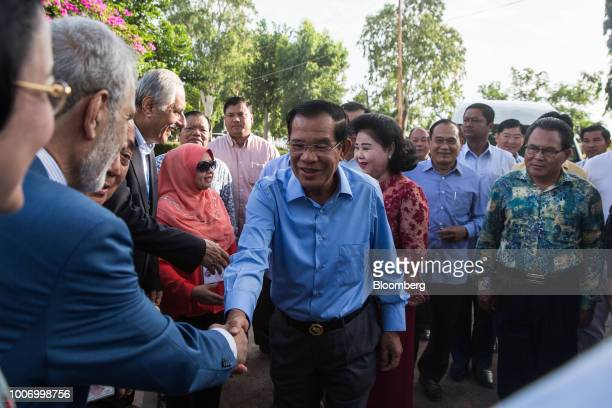 HunSenCambodia'sprimeministerandpresidentoftheCambodianPeople'sParty center shakes hands with a man as he arrives at a polling station to...