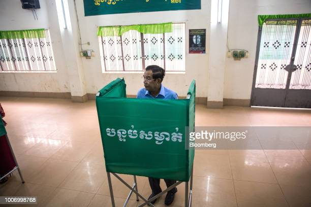 HunSenCambodia'sprimeministerandpresidentoftheCambodianPeople'sParty stands at a booth to mark his ballot for the general election at a...