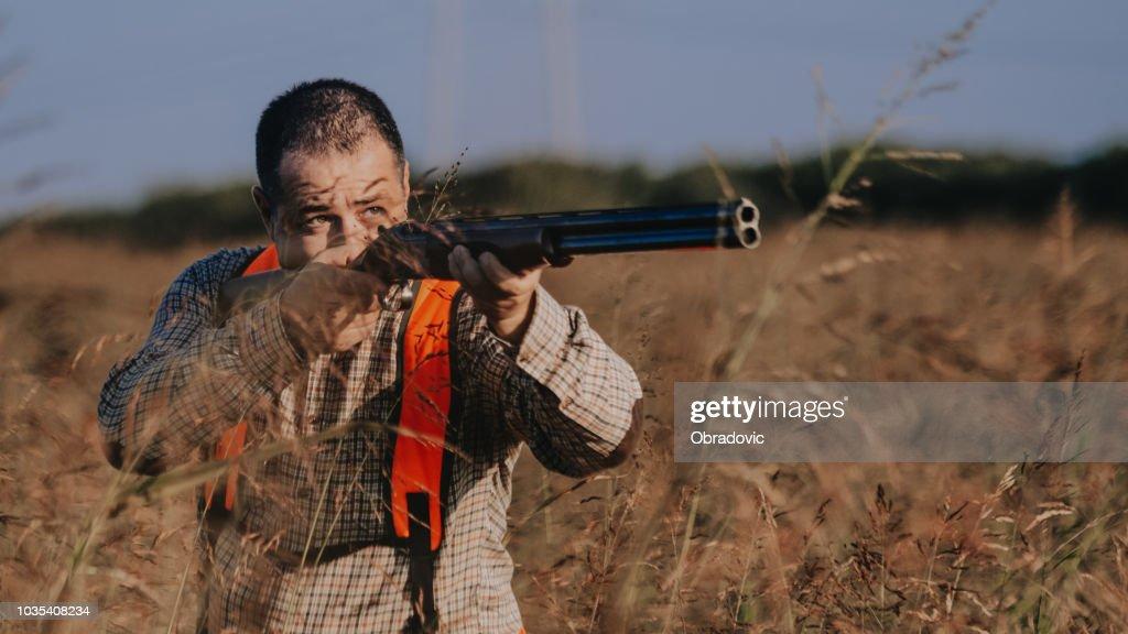 Hunter aiming bird : Stock Photo
