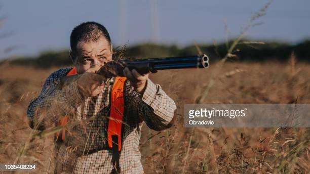 Hunter aiming bird
