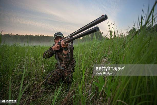 Hunter aiming rifle while kneeling on field against sky
