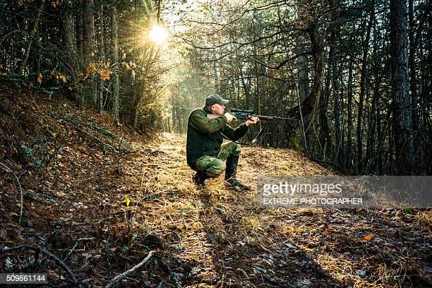 Cazador de apuntando con rifle en el bosque