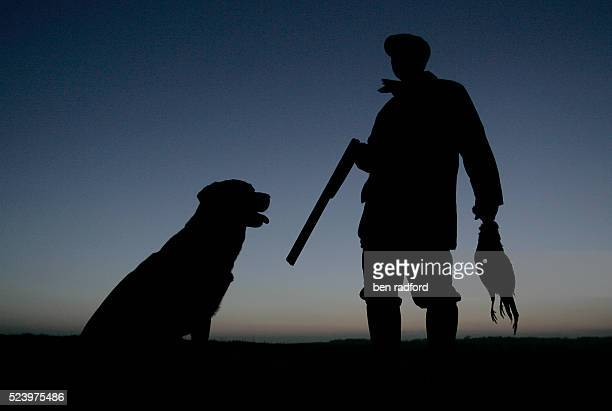 A hunter and his retriever dog are silhouetted against the winter sky during a pheasant shoot in North Newington near Banbury in Oxfordshire UK The...